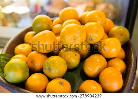 cooking, kitchen, vegetarian food, fruits and citrus concept - basket of of fresh ripe oranges fruits at kitchen - stock photo