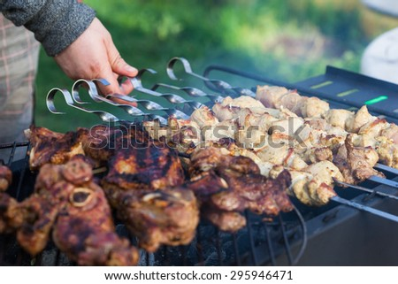 Cooking lamb steaks and pork kebab on grill, skewered pork meat in hand, outdoor. Selective focus and shallow DOF - stock photo