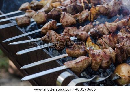 Cooking marinated shashlik or shish kebab, chiken meat grilling on metal skewer, close up. Selective focus - stock photo