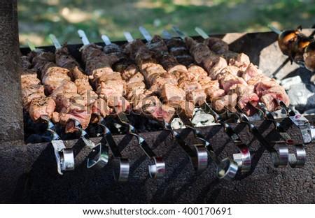 Cooking marinated shashlik or shish kebab, raw meat grilling on metal skewer, close up. Selective focus - stock photo