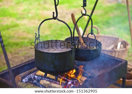 Cooking meal outdoors with pots on an open fire . - stock photo