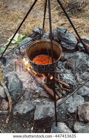 Cooking meat on a fire outdoors in cast-iron cauldron. Preparing food in a pan on a bonfire. Family holidays, summer picnic on the nature.
