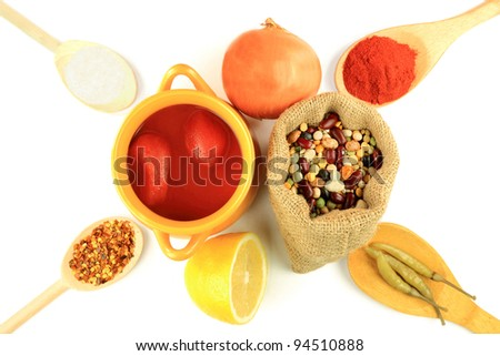 Cooking mix beans soup, beans in burlap bag, canned tomatoes in bowl, ingredients, seasonings in wooden spoons - red and crushed hot red paprika, Onion, Lemon, Sea Salt, hot jalapeno pickled pepper. - stock photo