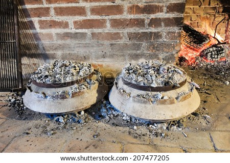 cooking of traditional dalmatian meal Peka in metal pots under burning coals - stock photo