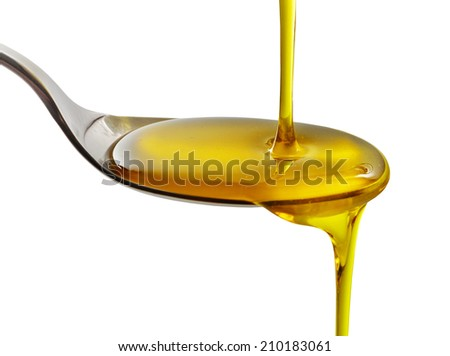 cooking oil pouring into spoon isolated on a white background