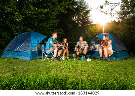 cooking on a camping with a group of young friends - stock photo