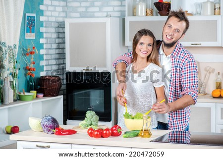 Cooking on Family kitchen. Young and beautiful loving couple cooking and help each other while preparing dinner with vegetables in the kitchen. - stock photo