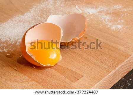 Cooking or baking background with close up broken egg, yolk in eggshell, flour on a wooden background - stock photo