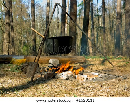 Cooking outdoors in cast-iron cauldron - stock photo
