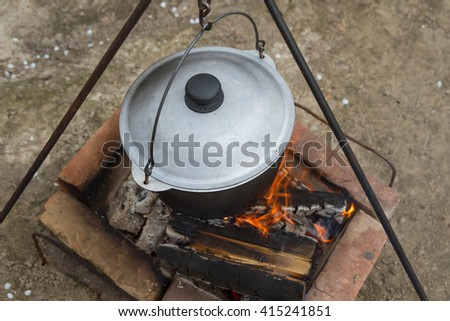 Cooking over a campfire in a cast iron pot. Cast iron pot for soup hanging over the fire campfire. Cooking over a fire in a kettle. - stock photo