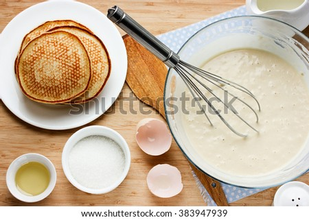 Cooking pancakes for breakfast. Ingredients for making pancakes, dough and fried pancakes on a wooden table - stock photo