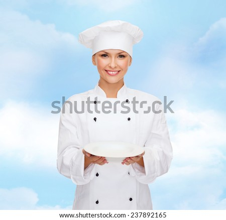 cooking, people and food concept - smiling female chef, cook or baker with empty plate over blue cloudy sky background - stock photo
