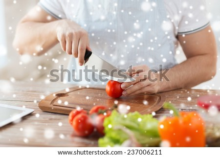 cooking, people, vegetarian food and home concept - close up of man chopping tomato and other vegetables on cutting board with big knife - stock photo