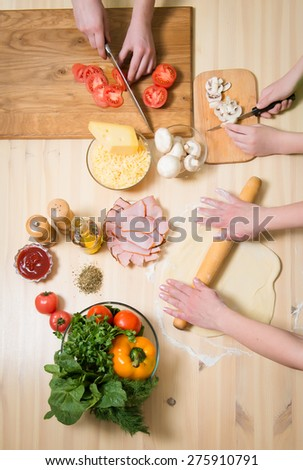 Cooking pizza at home. Filling pizza with ingredients. Top view of hands and table with ingredients. Overhead view. - stock photo
