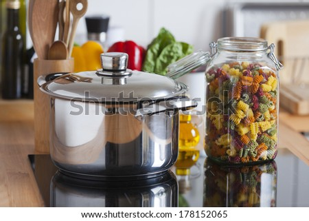 Cooking Pot and a Storage Jar with colorful Pasta with Copy Space in the upper and lower Area of the Image - stock photo