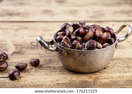 Cooking Pot filled with fresh Sweet Chestnuts from the Forest in Autumn - stock photo
