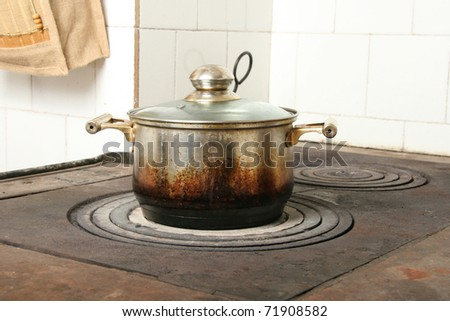 cooking pot on old kitchen stove - stock photo