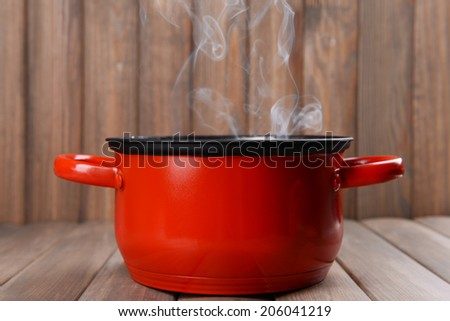 Cooking pot with steam on table on wooden background - stock photo