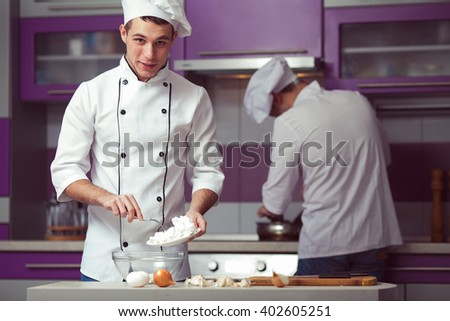 Cooking process concept. Portrait of two funny working men in cook uniform making food in modern kitchen. Indoor shot - stock photo