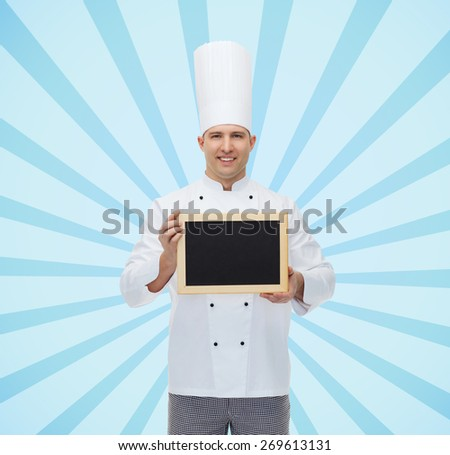 cooking, profession, advertisement and people concept - happy male chef cook showing and holding blank menu board over blue burst rays background - stock photo