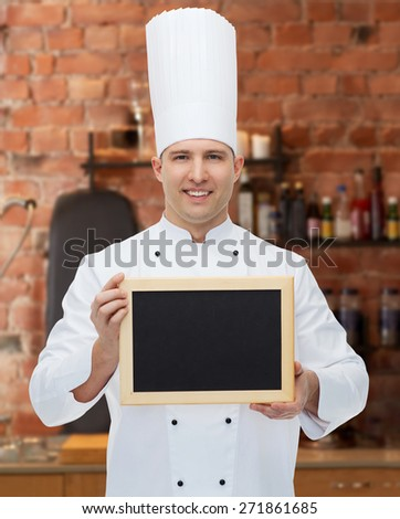 cooking, profession, advertisement and people concept - happy male chef cook showing and holding blank menu chalk board over kitchen background - stock photo