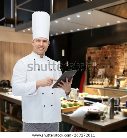 cooking, profession and people concept - happy male chef cook holding tablet pc computer over restaurant kitchen - stock photo
