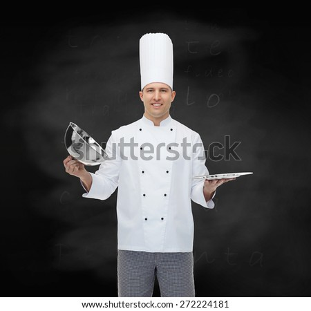 cooking, profession and people concept - happy male chef cook opening cloche cover over black chalk board background - stock photo
