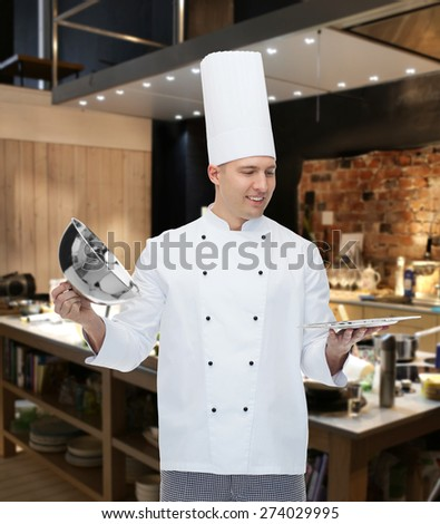 cooking, profession and people concept - happy male chef cook opening cloche cover over kitchen background - stock photo