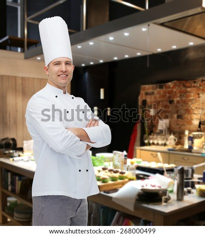 cooking, profession and people concept - happy male chef cook with crossed hands over restaurant kitchen - stock photo