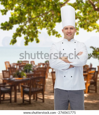 cooking, profession and people concept - happy male chef cook with crossed hands over restaurant lounge on beach - stock photo