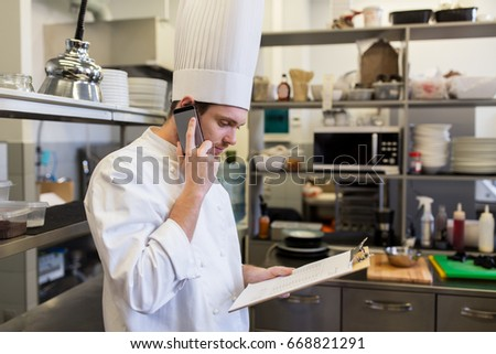 cooking, profession and people concept - male chef cook with clipboard calling on smartphone at restaurant kitchen