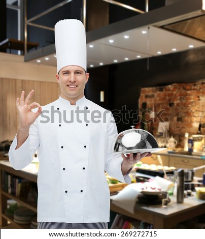 cooking, profession, gesture and people concept - happy male chef cook holding cloche and showing ok sign over restaurant kitchen - stock photo
