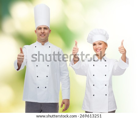 cooking, profession, gesture and people concept - happy male chef cook showing thumbs up over green background - stock photo