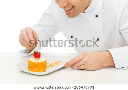 cooking, profession, haute cuisine, food and people concept - close up of happy male chef cook decorating dessert - stock photo