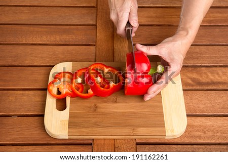 Cooking Red Bell Pepper. Man Cutting Red Bell Pepper on Cutting board - stock photo