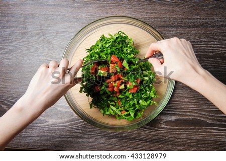 Cooking salad. Young woman cooking vegetable salad at home. Hands stirs vegetarian salad with fresh tomatoes, cucumber on wood table against dark background on rustic kitchen. Top view. - stock photo