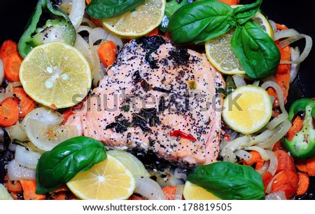 Cooking Salmon fillet in the pan with vegetables - stock photo