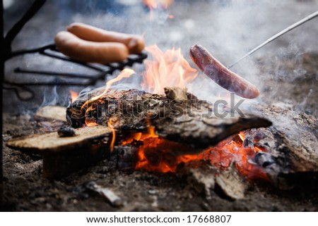 Cooking sausages by the campfire - stock photo
