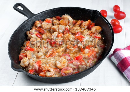 Cooking shrimp and cherry tomatoes in cast iron skillet - stock photo