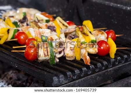 cooking skewers of seafood in a restaurant - stock photo
