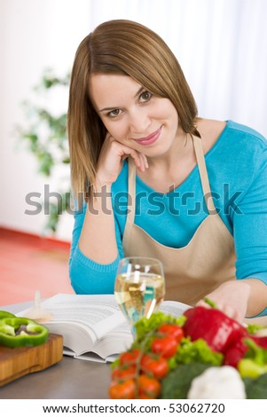 Cooking - Smiling woman with glass of white wine in kitchen with pasta and vegetable