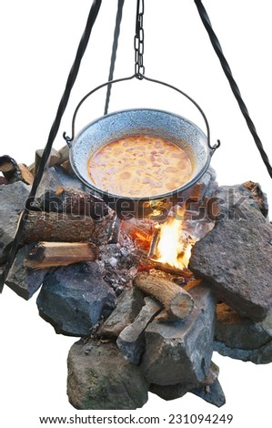 Cooking soup in cauldron over open fire, isolated with clipping path - stock photo