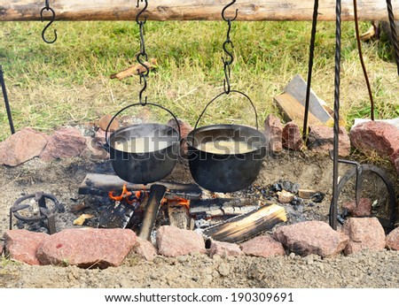 Cooking soup on the fire, delicious lunch in nature - stock photo