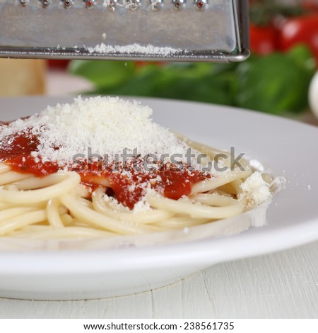 Cooking spaghetti noodles pasta food grating Parmesan cheese on plate - stock photo