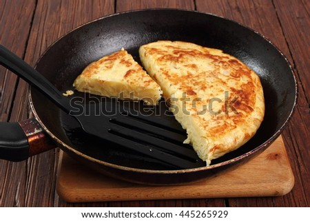 Cooking Spanish omelette in frying pan - stock photo