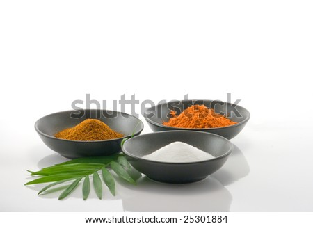 cooking spices in black bowls on white background with leaf - stock photo