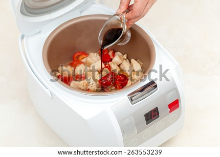 cooking stewed chicken with peppers and sauce in multicooker closeup - stock photo