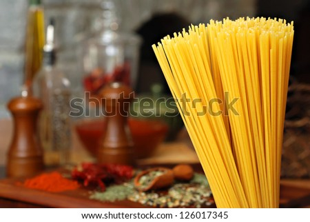 Cooking still life of uncooked spaghetti with arrangement of spices, herbs, olive oil, sauce, and peppers on wood table.  Rustic stone fireplace in background.  Macro with extremely shallow dof. - stock photo