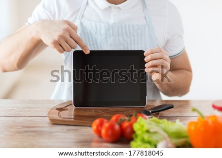 cooking, technology, advertising and home concept - close up of male hands holding tablet pc with blank black screen and pointing to it - stock photo