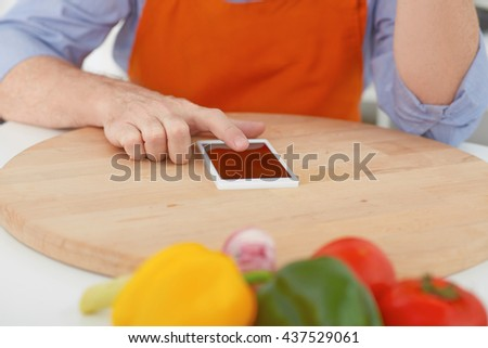 cooking, technology and home concept. Closeup man's hands  pointing finger on phone before cutting vegetables on a work surface in a kitchen.  - stock photo